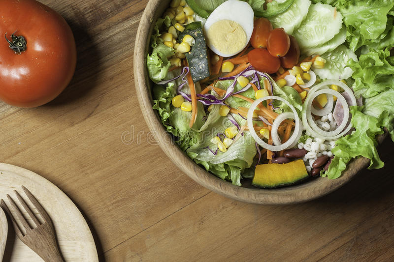 Healthy Salad Bowl Wood, wooden plates and cutlery on wooden floor. royalty free stock images