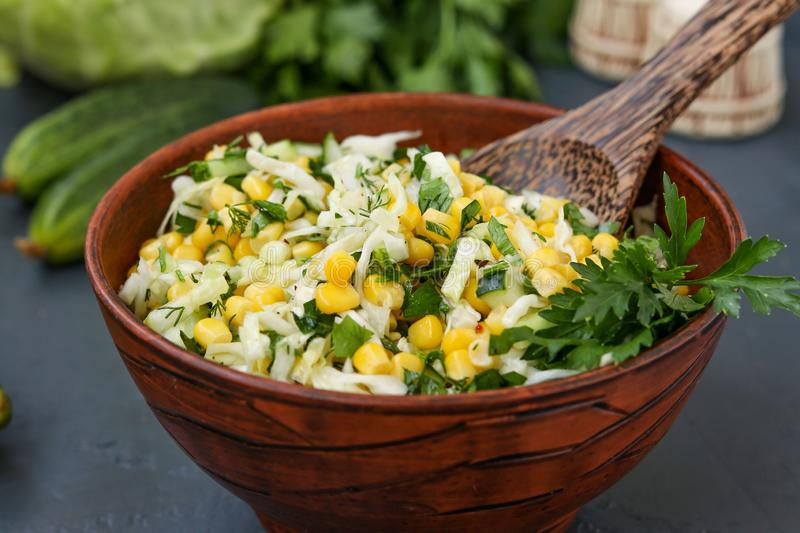 Healthy salad with cabbage, cucumbers, corn and parsley in a salad bowl on a dark background, horizontal photo stock image