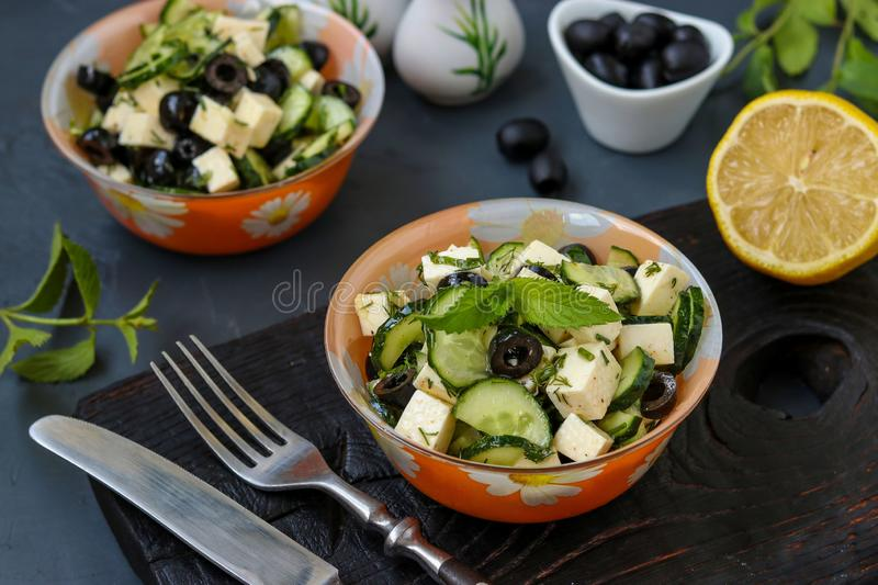 Healthy salad with cucumbers, feta and olives, with olive oil and greens, located in bowls against a dark background, horizontal stock photo