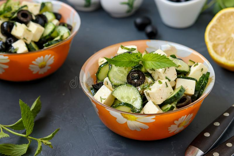 Healthy salad with cucumbers, feta and olives, with olive oil and greens, located in bowls against a dark background, horizontal stock images