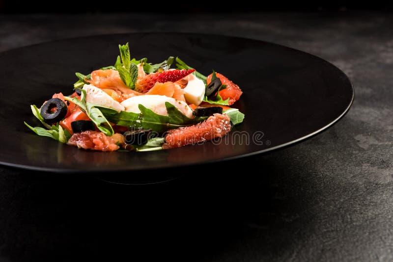 Healthy salad on dark plate.Restaurant dish,healthy eating stock image