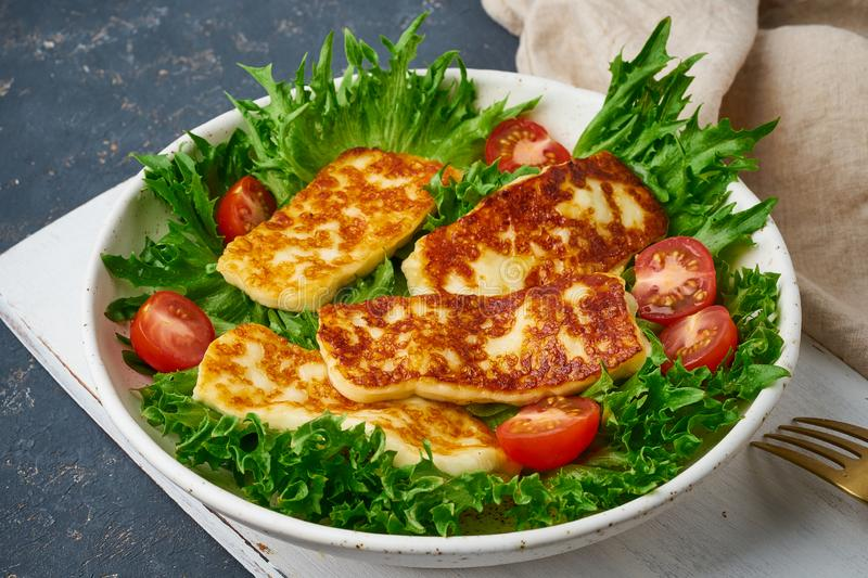 Healthy salad with fried halloumi and tomatoes, closeup, keto ketogenic diet royalty free stock photography
