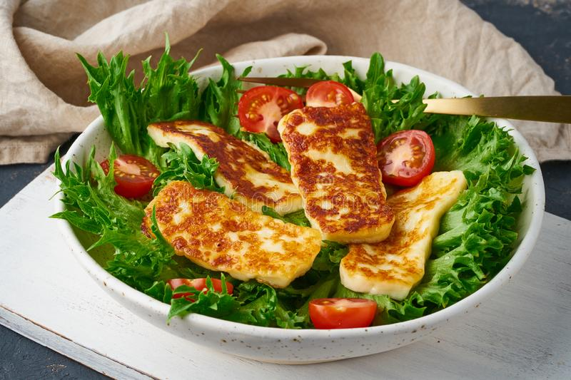 Healthy salad with fried halloumi and tomatoes, closeup, keto ketogenic diet stock photo