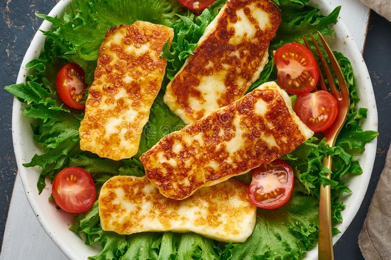 Healthy salad with fried halloumi and tomatoes, closeup top view, keto ketogenic diet. Vegeterian salad with fried halloumi and tomatoes, closeup top view, keto royalty free stock image