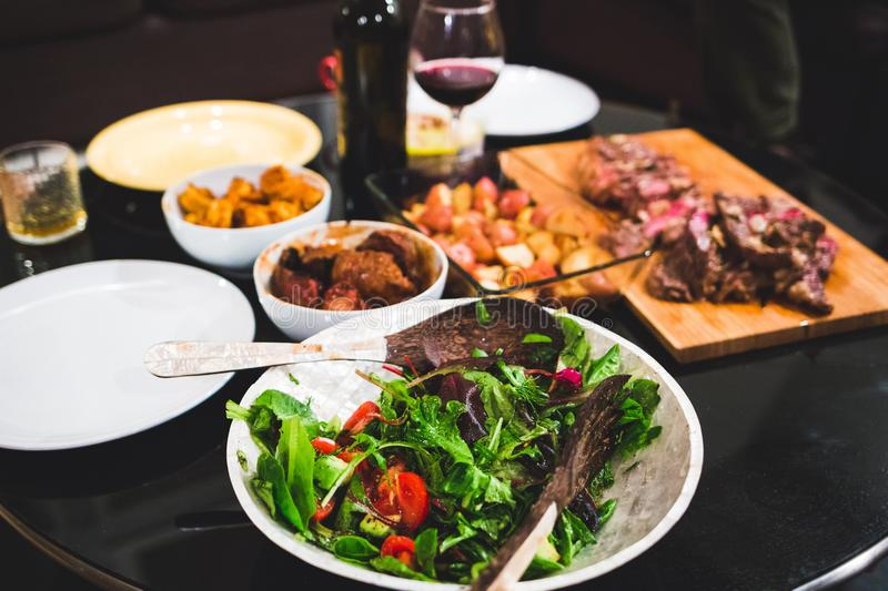 Healthy salad and meats dinner table. Dining royalty free stock images