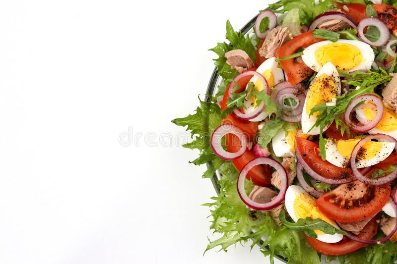 Healthy salad of organic salad with canned tuna, tomatoes, chicken eggs, arugula, red onion and microgreens stock images