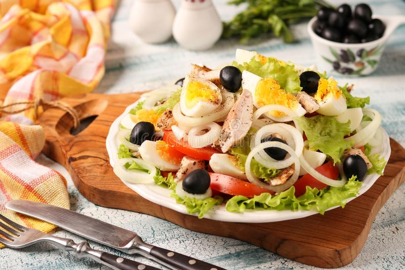Healthy salad of organic lettuce with chicken, tomatoes, eggs, black olives and white onions. On wooden board on blue background stock photo