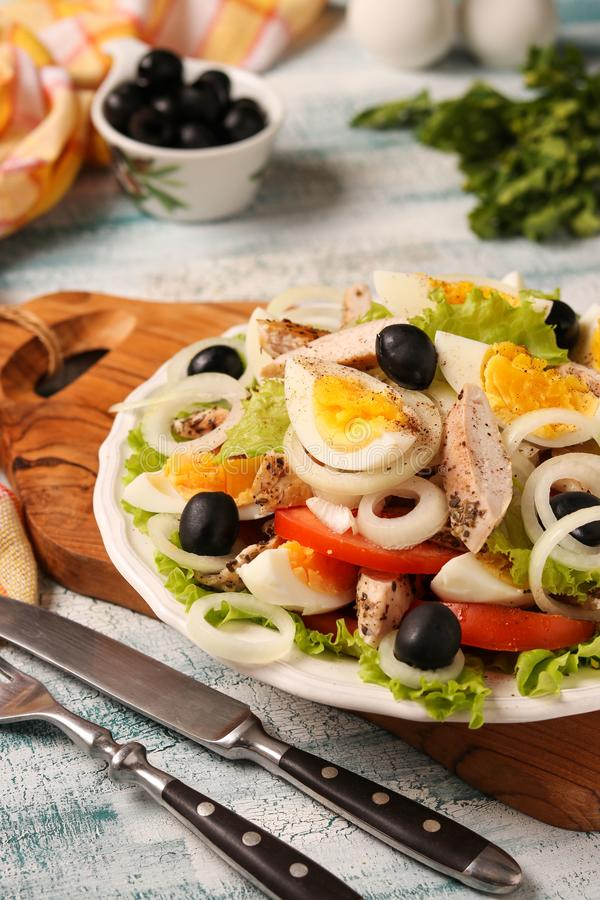 Healthy salad of organic lettuce with chicken, tomatoes, eggs, black olives and white onions. On wooden board on blue background stock images