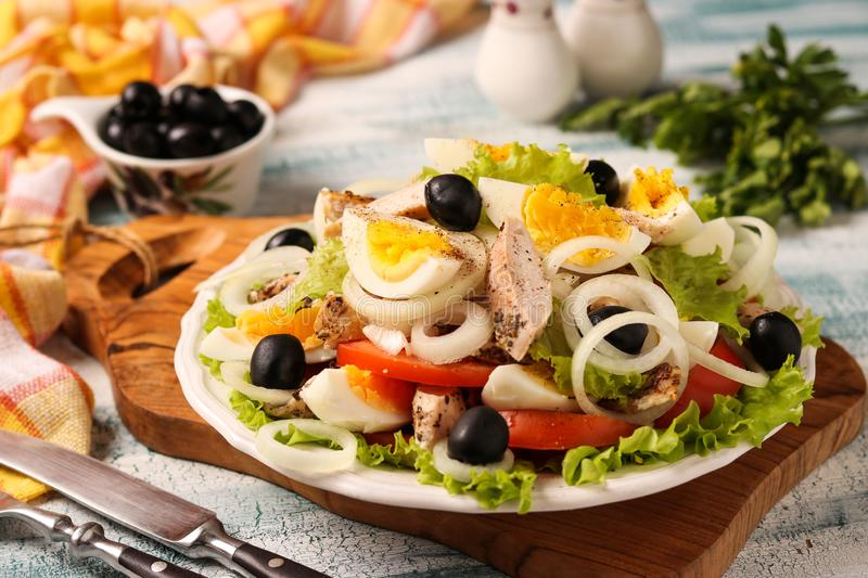 Healthy salad of organic lettuce with chicken, tomatoes, eggs, black olives and white onions. On wooden board on blue background royalty free stock photography
