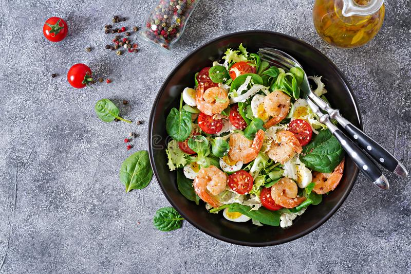 Healthy salad plate. Fresh seafood recipe. Grilled shrimps and fresh vegetable salad and egg. Grilled prawns. Healthy food. Flat l. Ay. Top view royalty free stock image