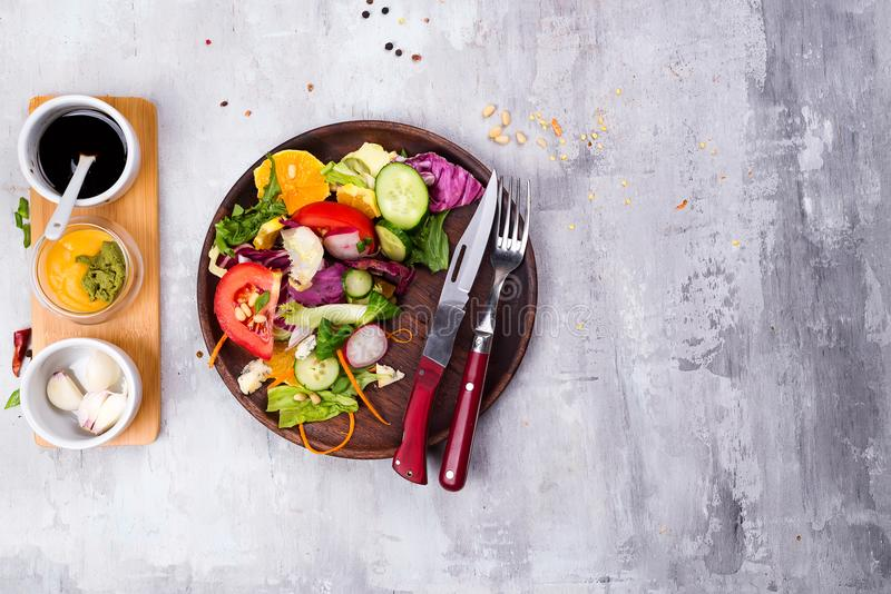 Healthy salad plate with vegetables on stone background p. Food and health. Clean eating. Healthy salad plate with tomato,orange, walnut, salad and cucumber stock photos