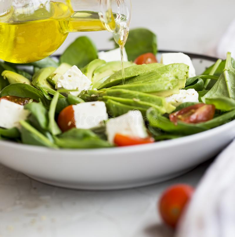 Healthy salad. Pouring olive oil over salad with avocado, feta c stock images