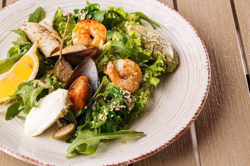 Healthy Salad. Recipe for fresh seafood. Grilled shrimps, mussels and squid, fresh salad lettuce and avocado puree royalty free stock photo