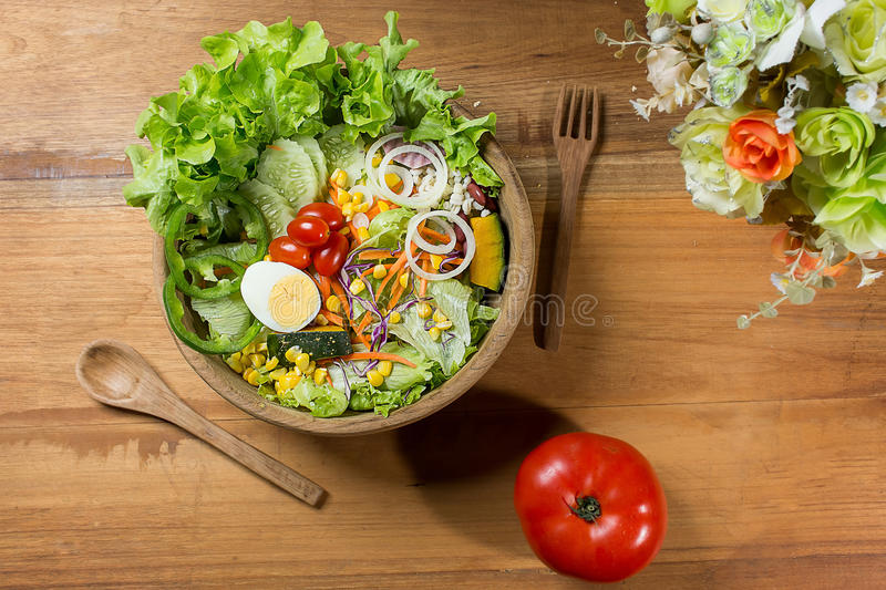 Healthy salad in wooden bowl with wooden plate. royalty free stock photo