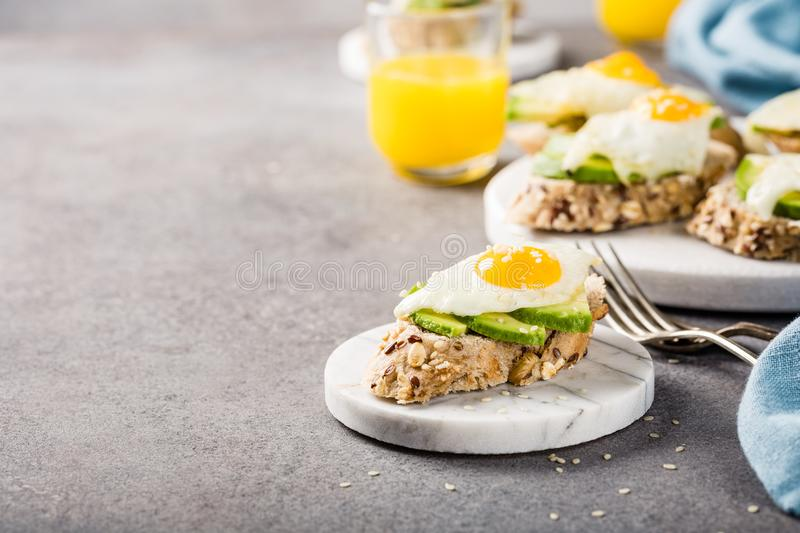 Healthy sandwich with fresh avocado and fried quail eggs. Healthy breakfast with open sandwich with fresh avocado and fried quail egg on small marble board on royalty free stock photo