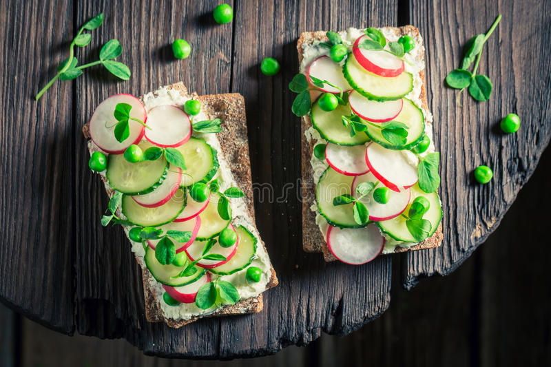 Healthy sandwich with fromage cheese, avocado and crunchy bread. On old wooden table royalty free stock image