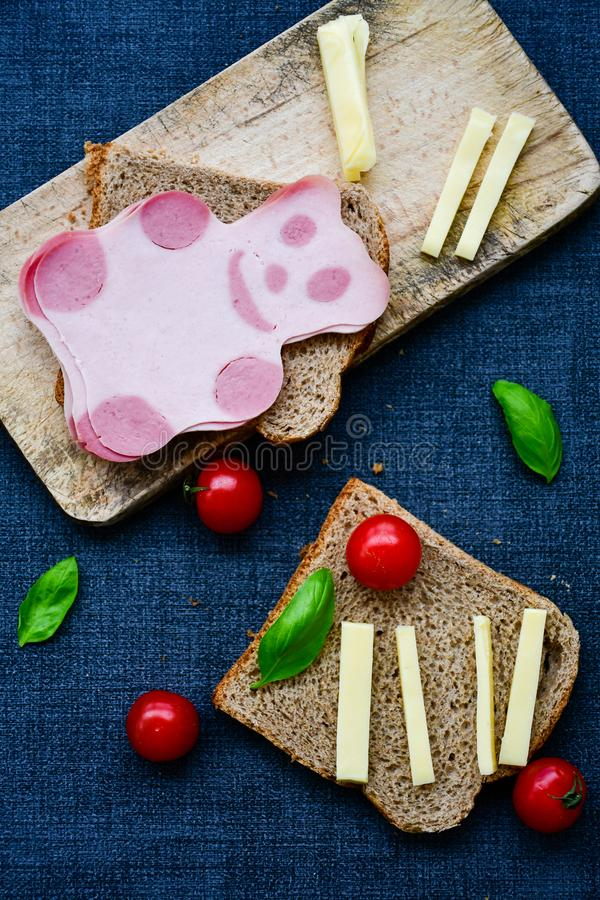 Funny bear face sandwich for kids. Healthy sandwich wits salami with bear face , basil, yellow cheese and cherry tomatoes stock photography