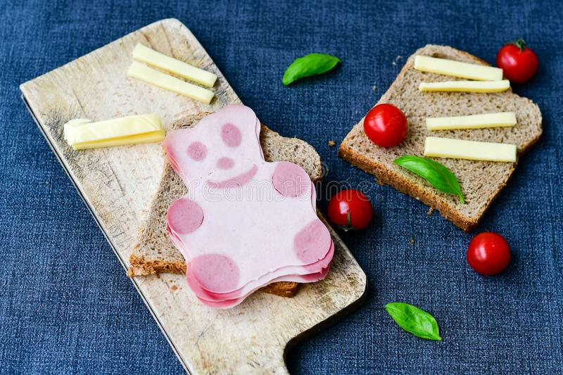 Funny bear face sandwich for kids. Healthy sandwich wits salami with bear face , basil, yellow cheese and cherry tomatoes stock photos