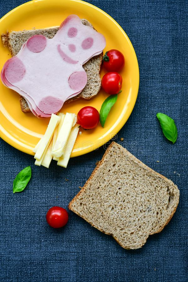 Funny bear face sandwich for kids. Healthy sandwich wits salami with bear face , basil, yellow cheese and cherry tomatoes stock photo