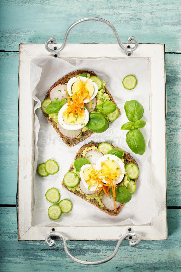 Healthy sandwiches. Healthy Vegetarian Sandwiches with Avocado, Tomato, Cucumber, Onion, Beetroot, Cream Cheese, Herbs and Spices on blue rustic background stock image
