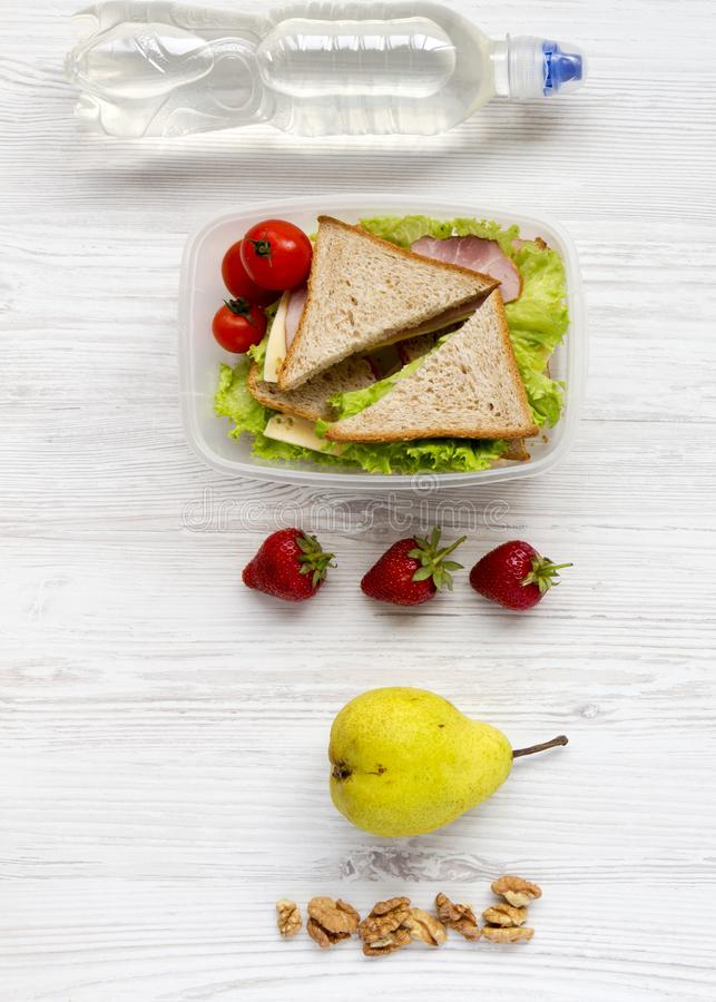 Healthy school lunch box with fresh fruits, walnuts, organic vegetables sandwiches and bottle of water on a white wooden surface, royalty free stock photos