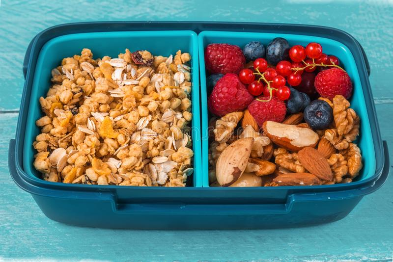 Healthy school lunch box with granola, nuts and berries to make healthy breakfast on blue wooden background royalty free stock images
