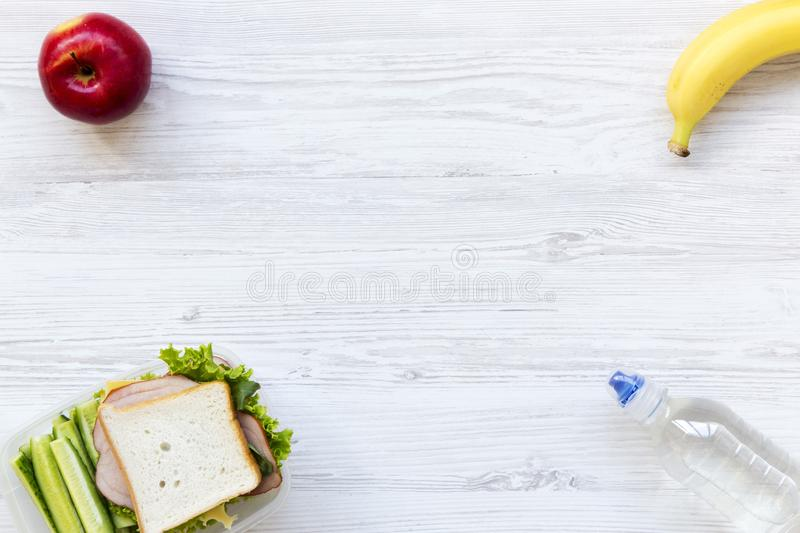Healthy school lunch box with sandwich, fruits and bottle of water on white wooden background, flat lay. From above. Copy space. royalty free stock photo