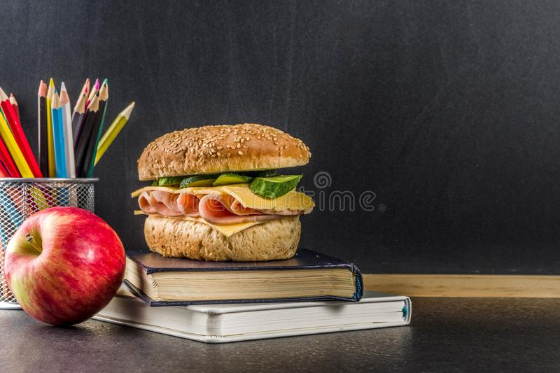 Healthy school lunch concept. Healthy school food concept, lunch with apple, sandwich, books and alarm clock on chalkboard background copy space stock images