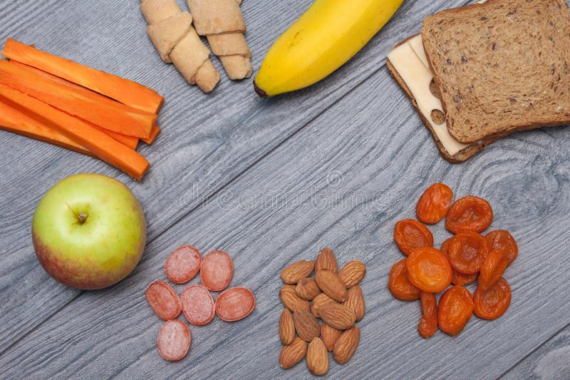 Healthy school lunch with sandwich with cheese, apple, banana, almonds, dry fruits, water, natural candies, carrot, biscuits on royalty free stock photography