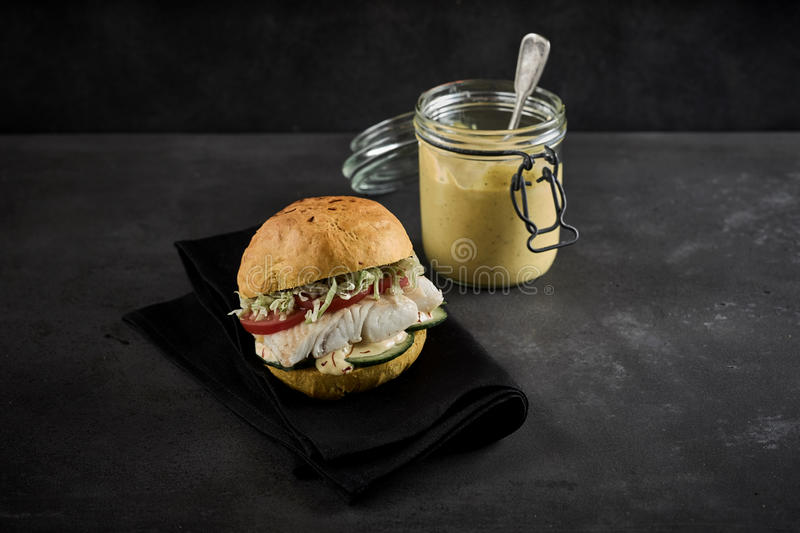 Healthy seafood burger with fresh pollock. Healthy seafood burger with a fresh pollock or coalfish fillet with salad trimmings served with a jar of mayonnaise on royalty free stock photography