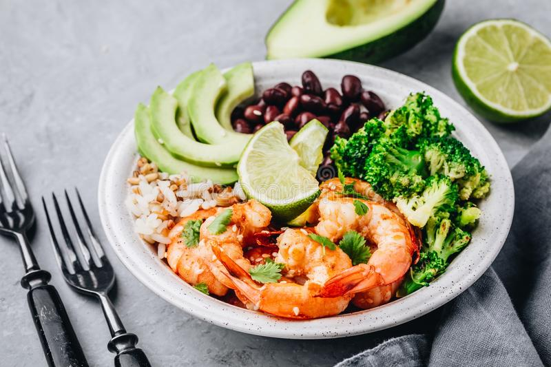 Spicy Shrimp Burrito Buddha Bowl with wild rice, broccoli, black beans and avocado stock photos