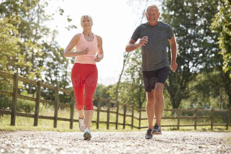 Healthy Senior Couple Enjoying Run Through Countryside Together royalty free stock images