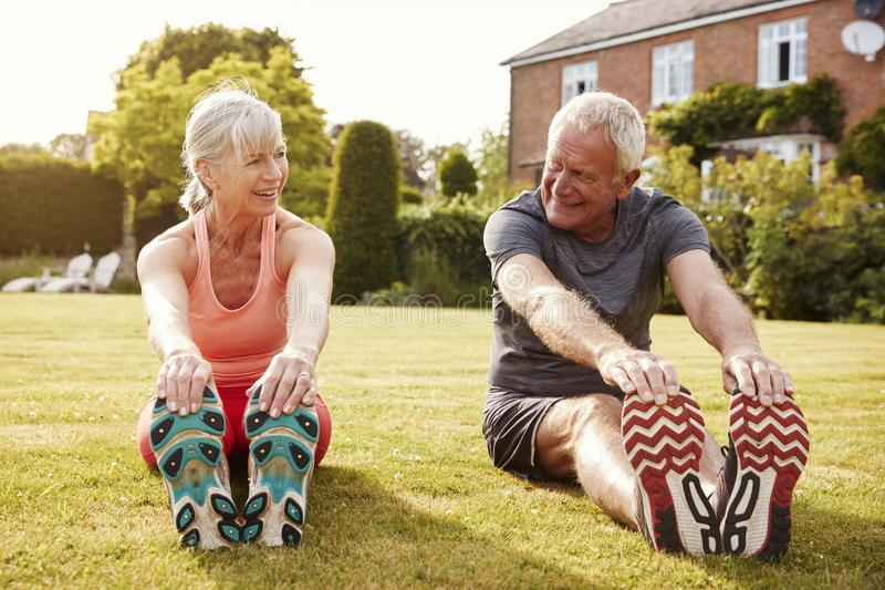 Healthy Senior Couple Exercising In Garden Together stock images
