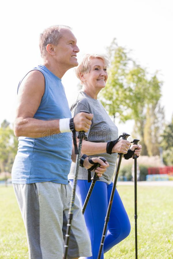 Healthy senior couple with hiking poles walking in park royalty free stock photography