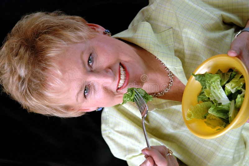 Healthy senior woman. A senior woman eating a green salad royalty free stock photo
