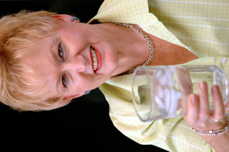 Healthy senior woman. A senior woman holding a glass of ice water( focus on woman royalty free stock photo