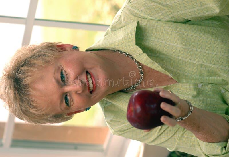 Healthy senior woman. A senior woman holding an apple stock photos