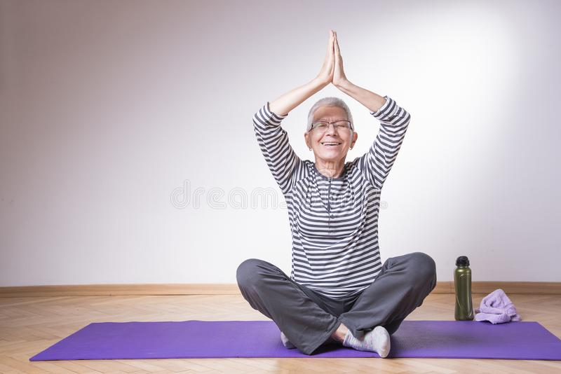 Active senior woman doing yoga. Healthy senior woman doing pilates or yoga, keeping herself relaxed and healthy stock photography