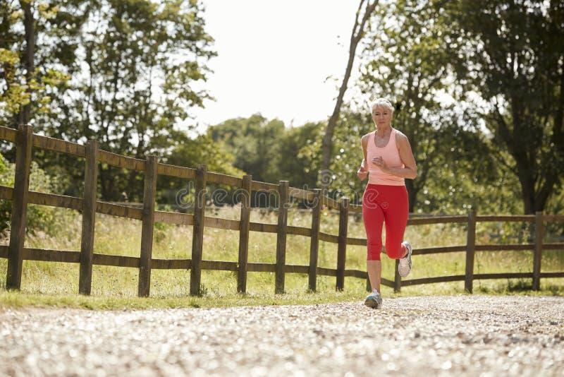 Healthy Senior Woman Enjoying Run Through Countryside royalty free stock photo