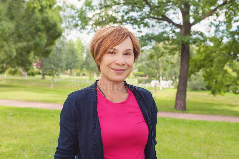 Healthy senior woman walking in park. Older woman with red short haircut outdoors. Mature beauty, 60s.  royalty free stock photos