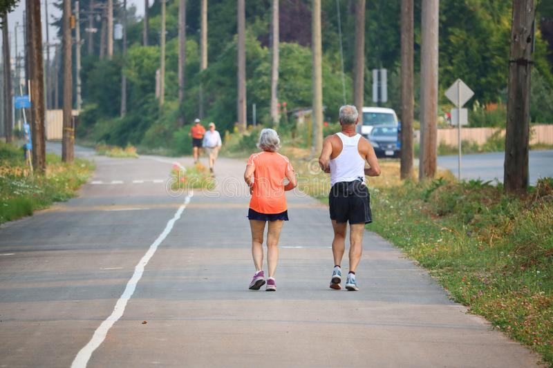 Healthy Seniors Staying Fit. Retired and active, a healthy couple stay fit by running together royalty free stock images