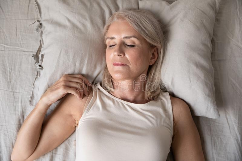 Healthy serene mature woman sleeping alone in bed, top view royalty free stock photos