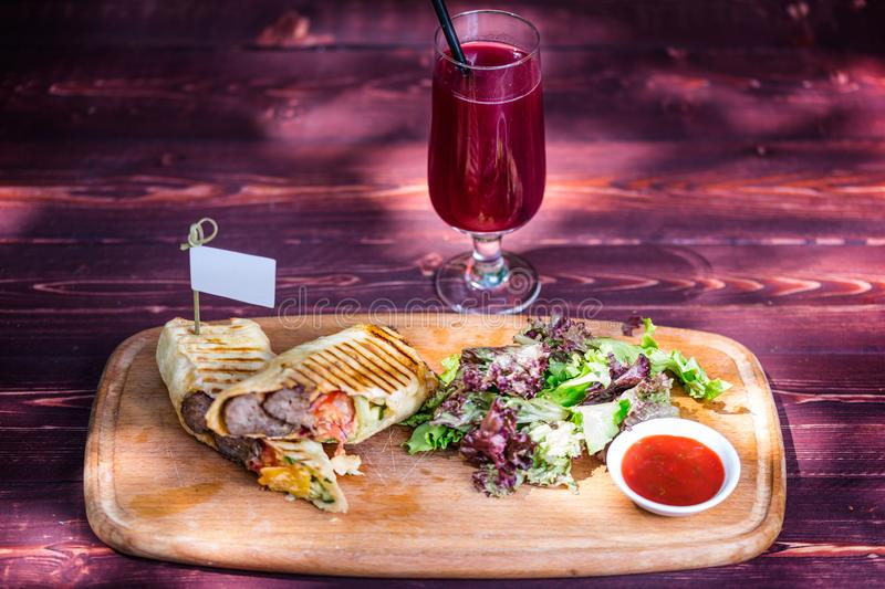Healthy shawarma sandwich with beef, green salad, sauce and lemonade. On the cutting wooden board, and wooden background stock photos