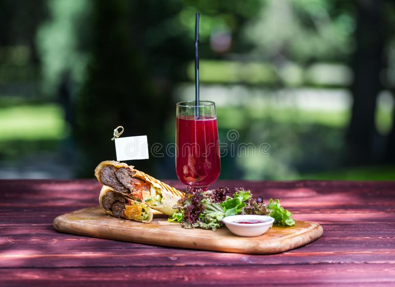 Healthy shawarma sandwich with beef, green salad, sauce and lemonade. On the cutting wooden board, and green summer stock photo
