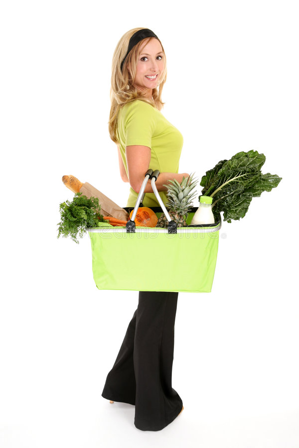 Healthy Shopper. Woman with a shopping bag filled with nutritious fruit and vegetables stock photography