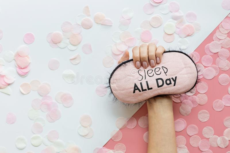 Healthy sleep concept. Female hand holding Sleeping mask on pink background with confetti. Flat lay, top view copy space, mockup, royalty free stock images