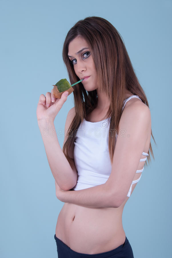 Healthy slim young woman, holding a straw in kiwi stock photos