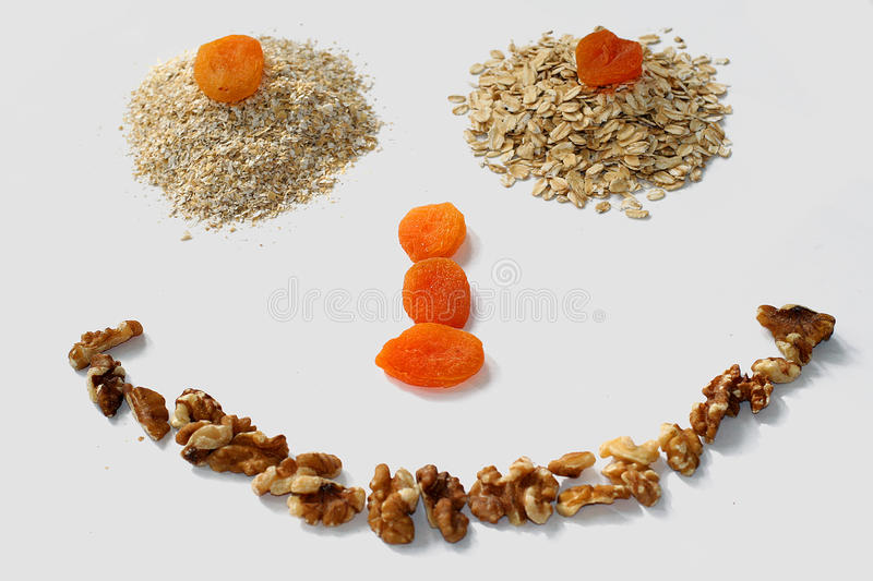 Healthy smile. Made out of oat bran, oats, dried apricots and walnuts stock photos