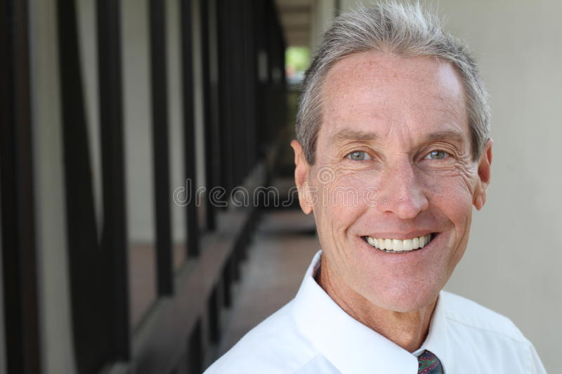 Healthy Smile. Teeth Whitening. Beautiful Smiling Young man Portrait close up. Over modern corridor background . Laughing stock photos