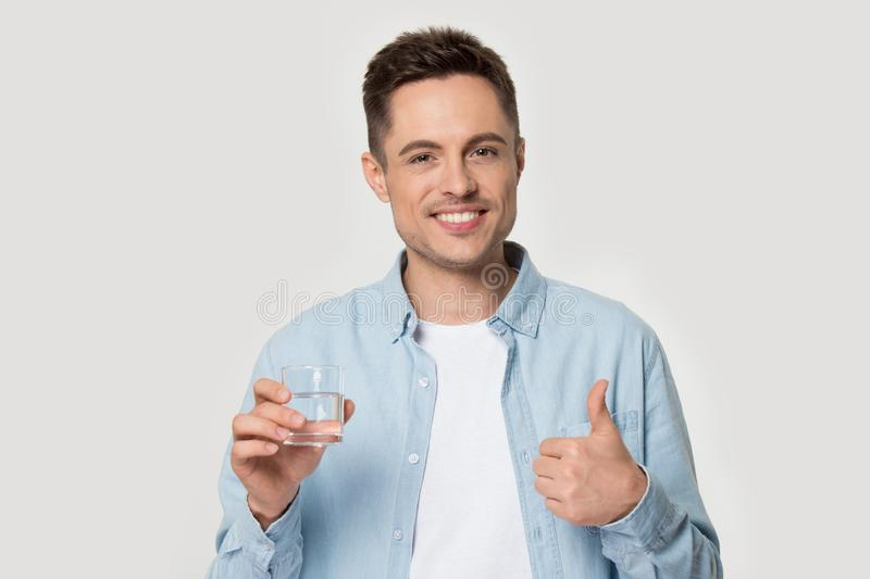 Healthy smiling man holding glass of water showing thumbs up stock photos